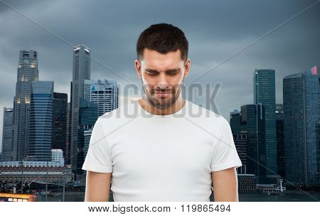 emotion, sadness and people concept - unhappy young man over evening singapore city background