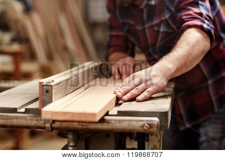 Plank of wood being cut with circular saw in workshop