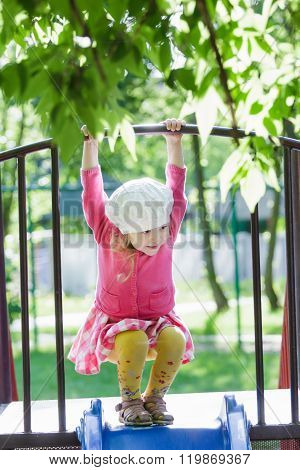 Three years old girl playing at playground slide and hanging on crossbar