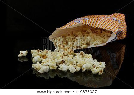 A Bag With Popcorn On Black Background