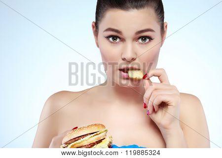 Funny girl eating hamburger on grey background