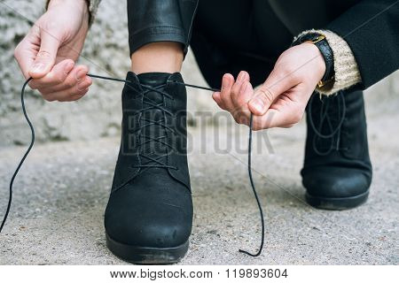 Woman In Elegant Clothes Tying Shoelaces On Shoes Close Up