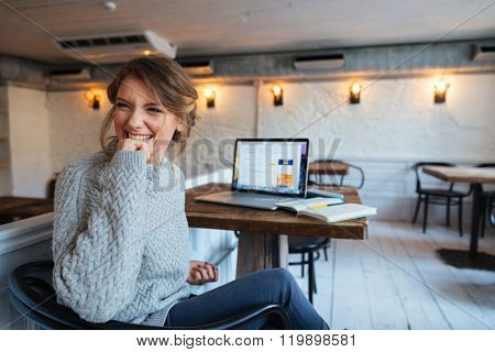 Cheerful woman sitting at the table with laptop computer in cafe and looking away
