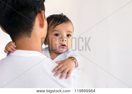 Young mexican father holds his six month baby boy