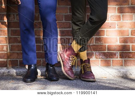 Closeup of the shoes of two men with elegant and casual boots