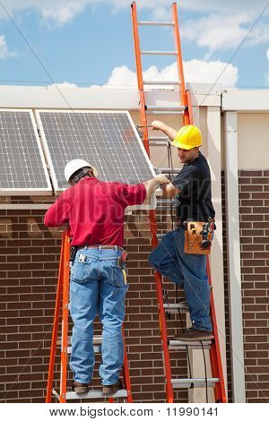 Construction electricians installing solar panels on the side of a building.