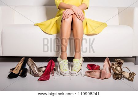 Woman sitting on couch and trying on shoes