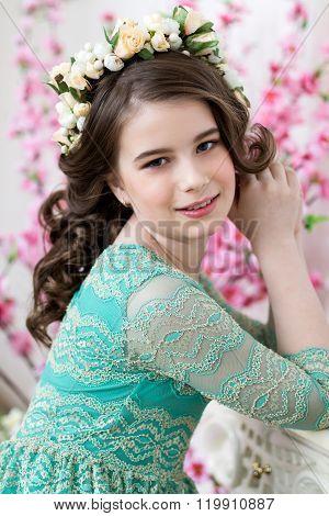 Portrait Of A Cute Little Girl In A Flower Wreath