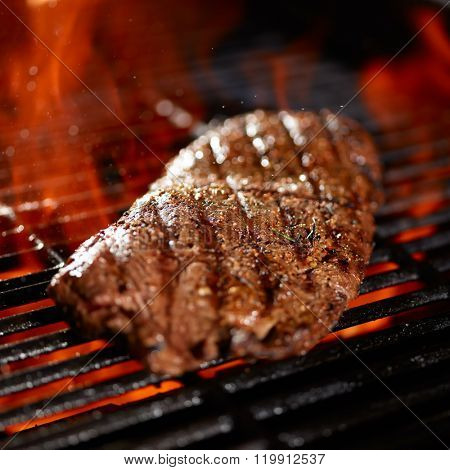 flat iron steak being cooked on flaming grill