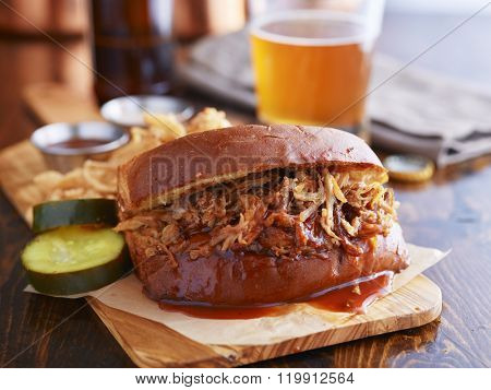 barbecue pulled pork sandwich with beer in the background
