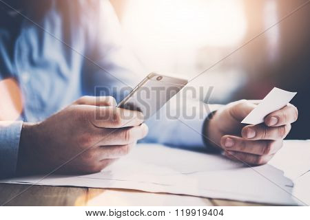 Business concept. Businessman holding hand white businesscard and making photo smartphone. New work