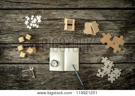 Various Cubes, Pegs, Puzzles And A Key Lying On Wooden Desk Around An Open Notepad