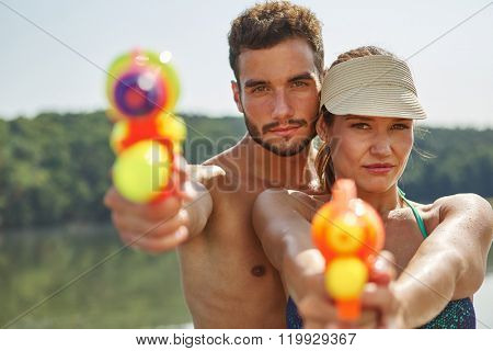 Couple aiming with squirt guns in summer on their holidays