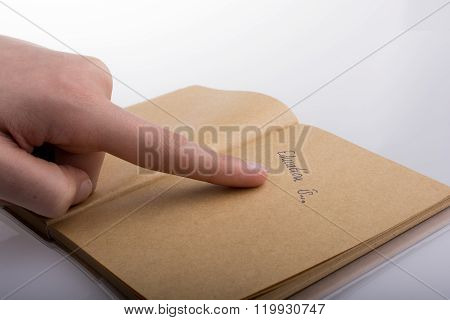 Hand Pointing On A Notebook