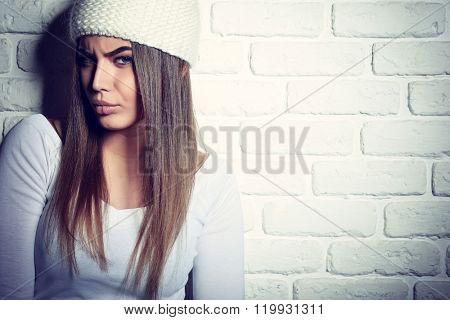 Portrait of young attractive cheerful hipster girl making funny faces, studio shot over white bricks background. Image toned.