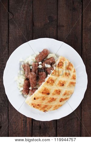 Cevapcici, bosnian minced meat kebab served with diced onion and somun bread