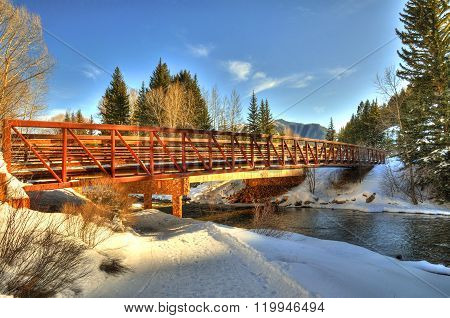 Hiking trail bridge over a river in Aspen Colorado on a clear day
