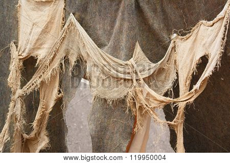 Photo shows close-up of medieval rags waving on the wall during a day.