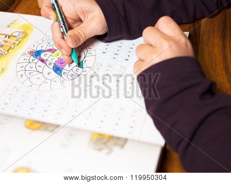 Child writes numbers in a booklet detail