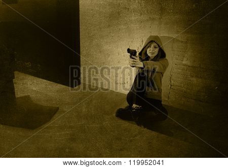 young teenager woman abused suffering internet cyber bullying scared screaming desperate in fear face expression sitting on the floor pointing gun to computer monitor in cyber bullying