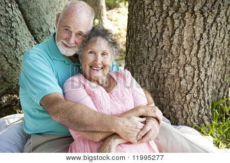 Beautiful senior couple in love, embracing under a tree.