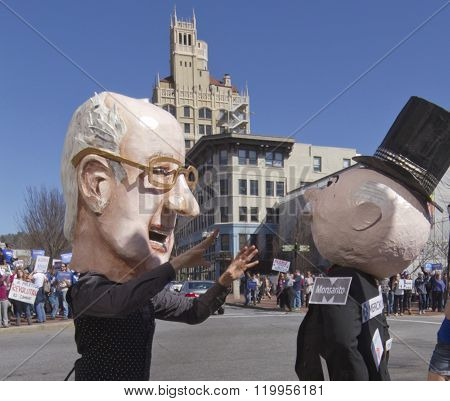 Asheville, North Carolina, USA - February 28, 2016: Humorous Bernie Sanders character confronts Mr. Monopoly effigy in front of his rally supporters on the streets of downtown Asheville NC