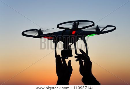 Flying drone with camera on the sky at sunset