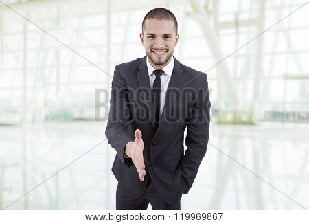young man in suit offering to shake the hand at the office