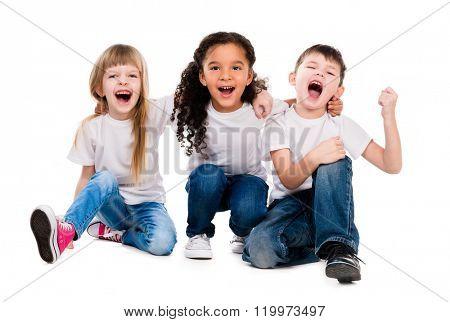 three funny trendy children laugh sitting on the floor