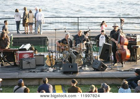 NEW YORK - JULY 1: Blues singer John Hammond (C) performs at Wagner Park with drummer Neil Gouvin (C-R), bassist Marty Ballou (R) and keyboardist Bruce Katz (L) on July 1, 2010 in New York City.