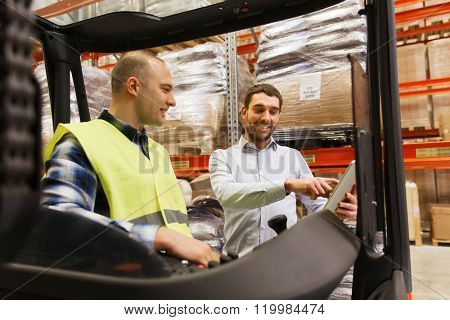 wholesale, logistic, loading, shipment and people concept - smiling loader on forklift and businessman with tablet pc computer at warehouse