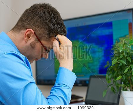 Handsome male meteorologist in glasses thinking over map background