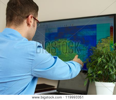 Handsome male meteorologist working with touchscreen. Back view