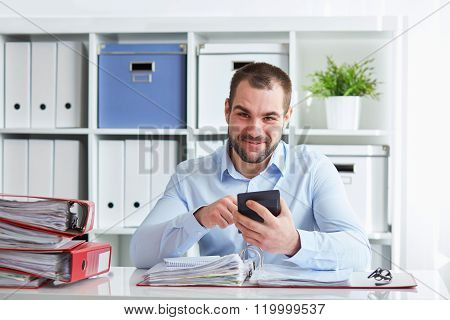 Smiling Businessman Calculates Taxes At Desk In Office