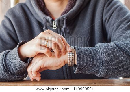 Woman Checks The Time On A Wrist Watch