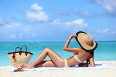 Sexy bikini woman tanning relaxing on beach. Suntan concept. Unrecognizable female adult from the back lying down with straw hat sunbathing under the tropical sun on Caribbean vacation. poster