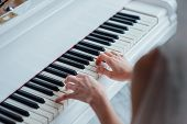 Close up of hands playing white piano. Concept of music and entertainment. poster