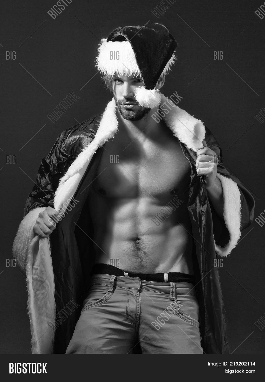 a2aca559e5fb7 Handsome santa claus guy sexy young bearded macho christmas man model in  red xmas or new