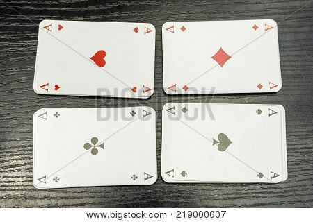 Four aces from a deck of playing cards on the table.