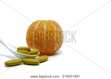 Fresh orange fruit and pills of vitamin C in spoon on white background, medical and healthcare concept