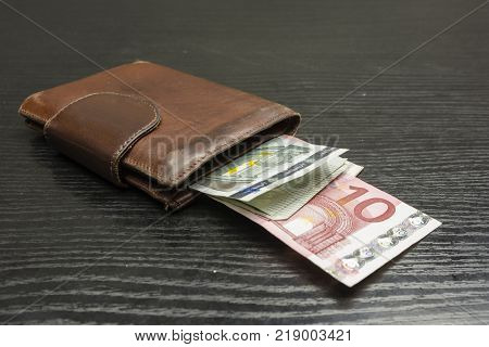 Euro banknotes in various denominations ejected from a brown wallet on the table.