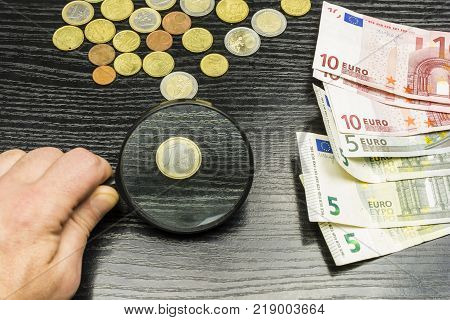 Money on the table. One euro coin enlarged by a magnifying glass.