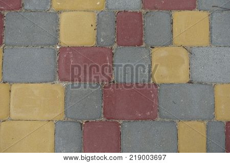Red yellow grey concrete pavement blocks from above