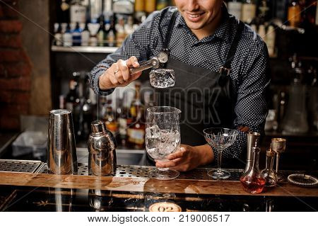 Bartender crushing a big ice cube on the bar counter with a special bar equipment on it for making a cocktail