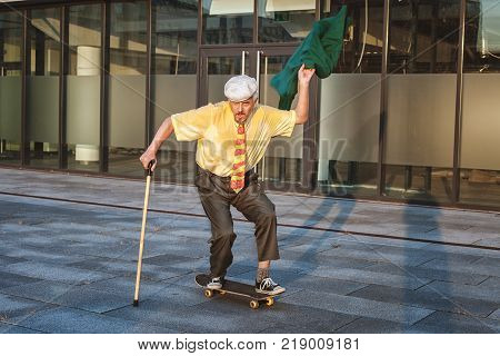 Old man is riding on a skateboard in his hand a walking stick.
