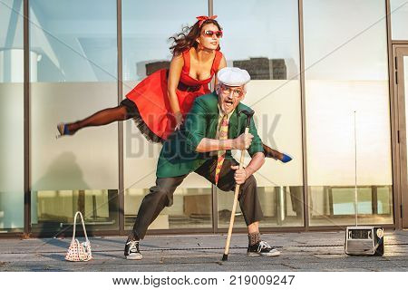 Woman jumps during a dance she dances with an old man.