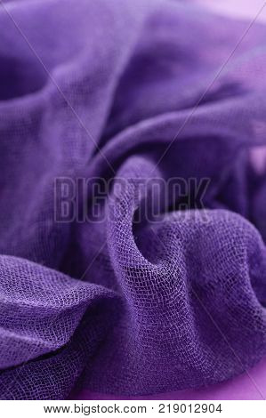 Closeup of hand dyed gauze fabric in purple and turquoise blue color. Colorful fashion cloth texture background. Ultra violet trendy color concept