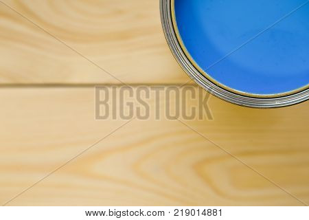 Redecorating house. A tin can of blue oil paint on a light uncolored wooden background. Close up. Top view. Space for your text or pruduct display.