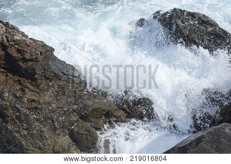 The Waves Breaking On A Stony Beach, Forming A Spray. Wave And Splashes On Beach. Waves Crashing Ont