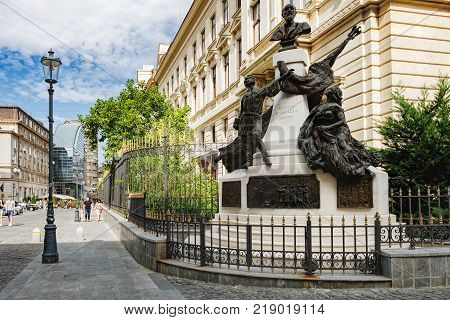 Bucharest, Romania - September 9, 2017: Tourists visiting the historical center Lipscani Street with its beautiful architecture, Bucharest, Romania. Monument to Eugeniu Carada in the foreground.